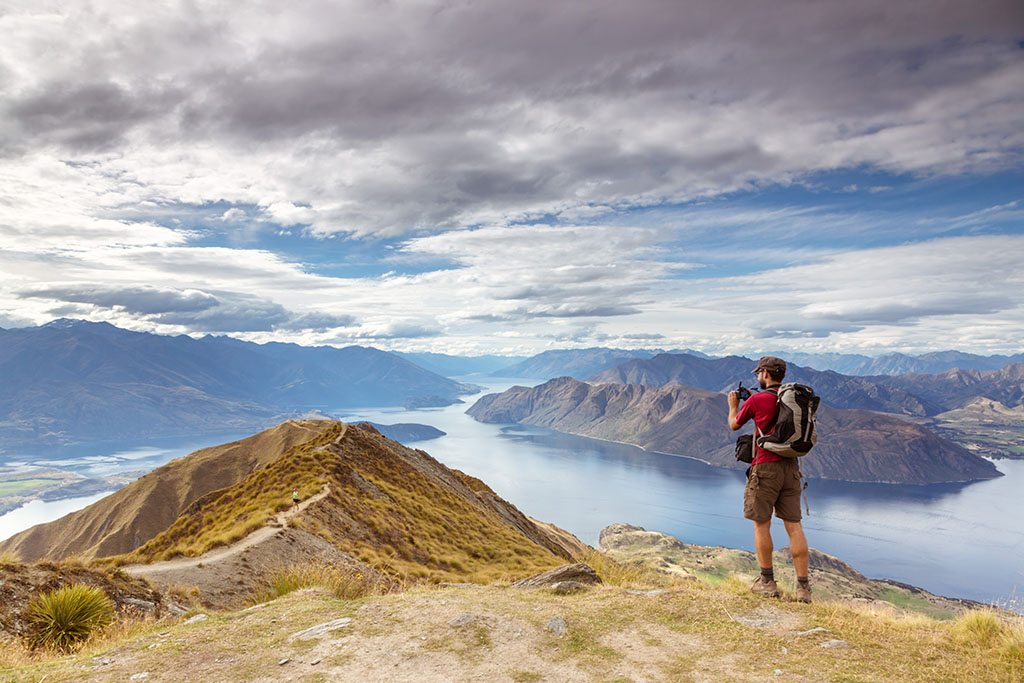 Man taking photo of scenic landscape in New Zealand.