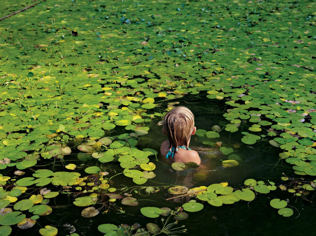 Maddie Roark swims among lily pads in her family's pond in western North Carolina. Her father runs an outdoor education center. In a recent study, some 70 percent of U.S. mothers reported that they played outside every day as children; only 31 percent of their children do.