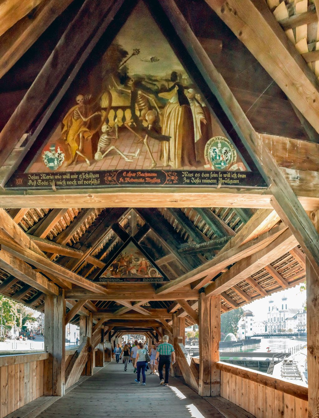 The triangular arches inside Lucerne's 13th-century Spreuerbrücke (Spreuer Bridge) has paintings representing the Danse Macabre. The paintings inside this covered wooden bridge feature different aspects of medieval life. What is common to all of them is a grinning skeleton reminding passersby of the inevitability of death. Photo: Van Der Meer Rene/Prisma/Dinodia