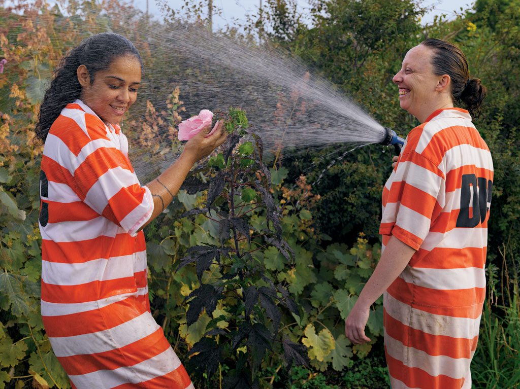 Inmates Vanessa Eranzo and Lauren Hughes (who've since been released) relax while working in a garden on Rikers Island, a New York City jail. Research suggests interacting with nature makes prisoners less violent.