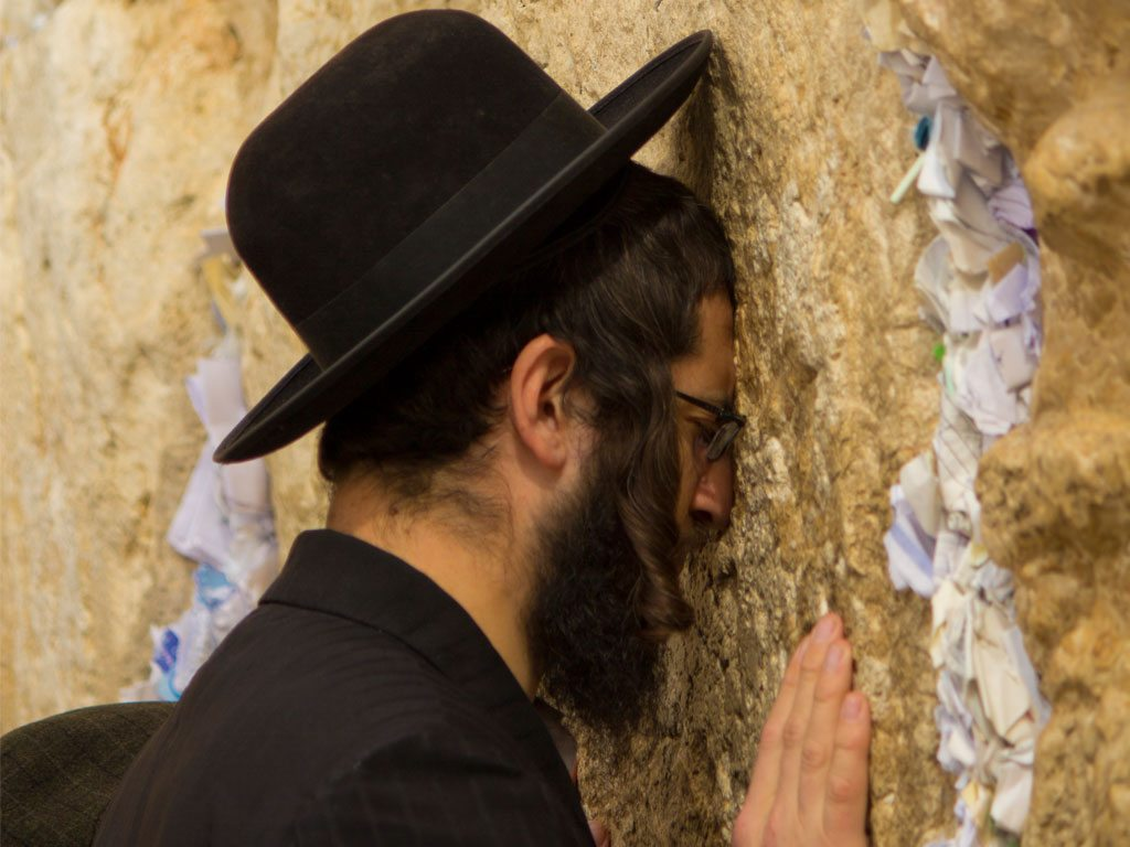 A Jewish man prays silently at the West Wall in Jerusalem. Pilgrims write their prayers on pieces of paper and wedge it between the Wall's crevices. Photo: Tali Budlender & Nick Logan/Lonely Planet Images/Getty Images