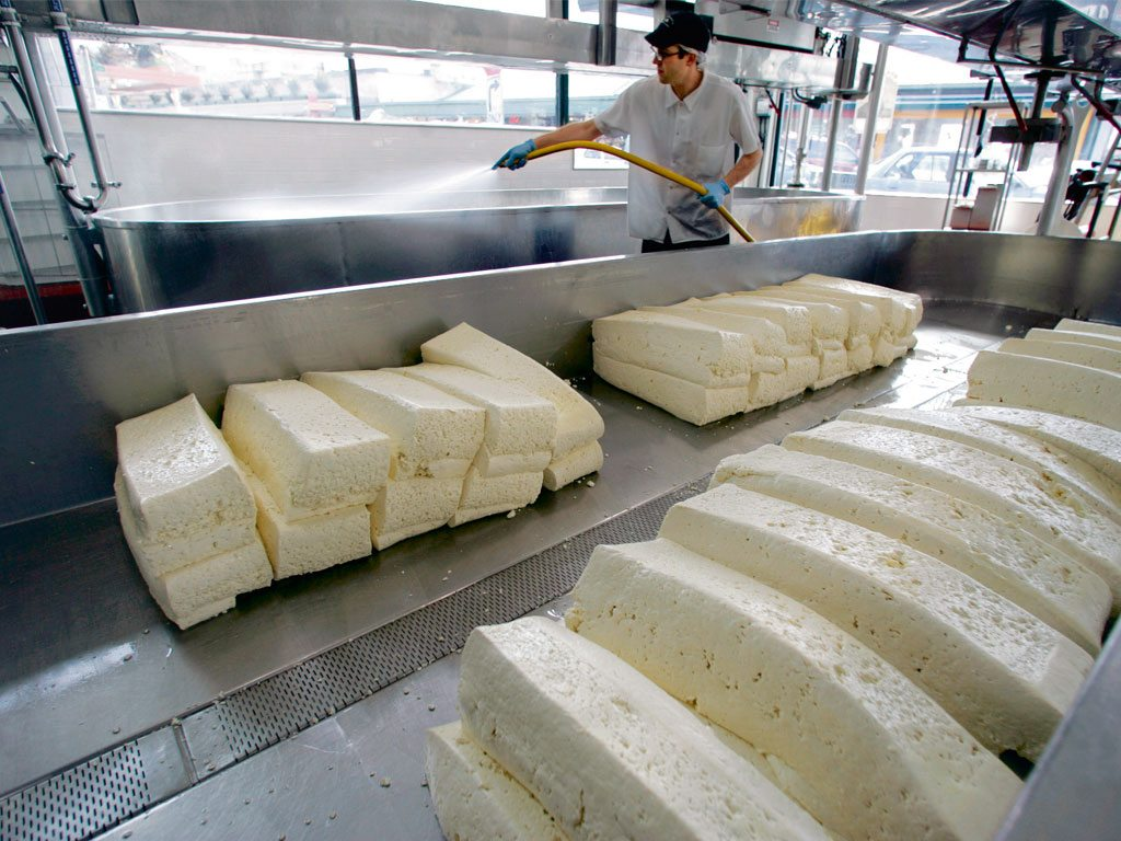 Cheese loaves undergo cheddaring, a process by which they are cut and compressed to release excess moisture and reduce acidity. Photo: Bloomberg/Contributor/Getty Images