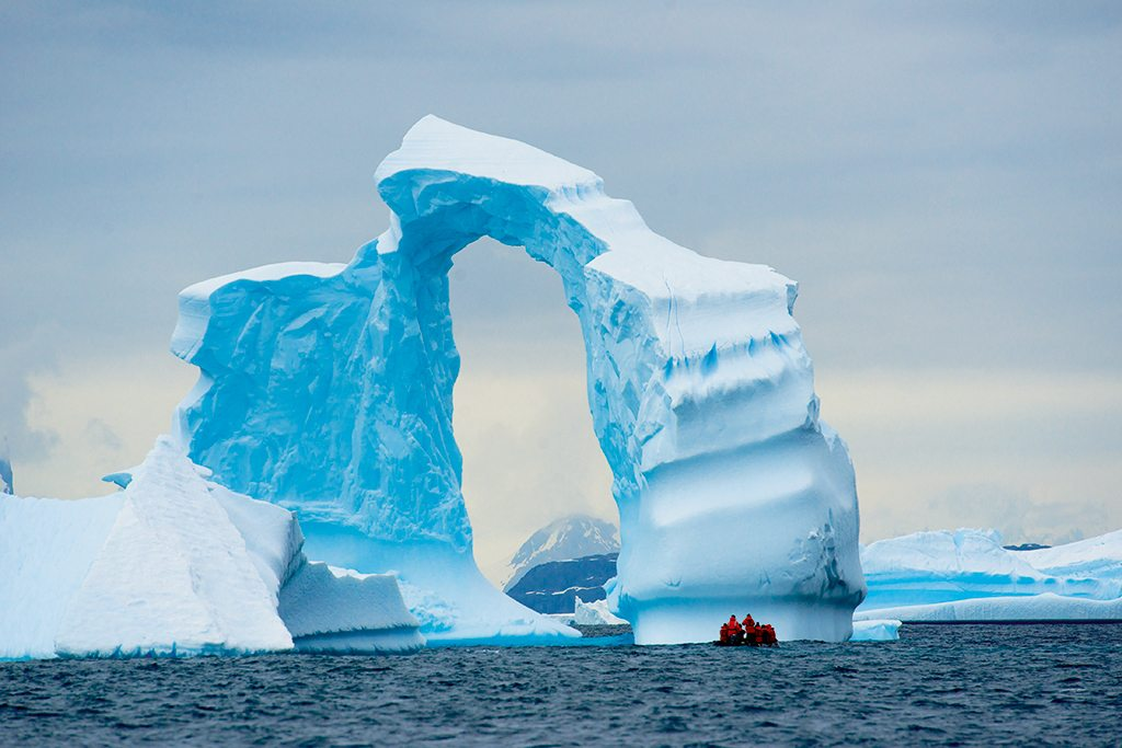 A towering ice arch offers expedition members the ultimate photo op. Photo: Cotton Coulson and Sisse Brimberg
