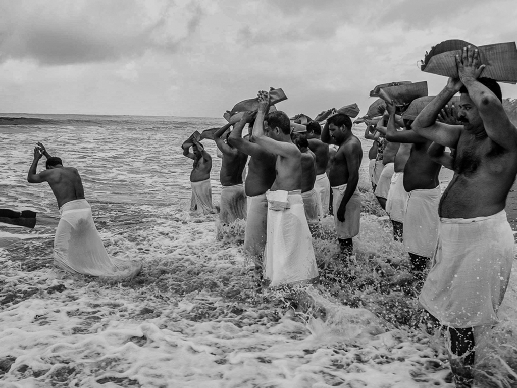 Men offer rice and sesame to their ancestors and pray for their souls on the occasion of Karkidaka vavu bali at a beach near Kozhikode, Kerala.