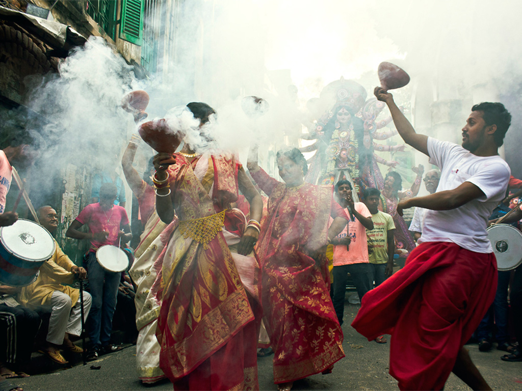 Devotees perform the dhunuchi dance with burning clay lamps during the Durga Puja festival in West Bengal.