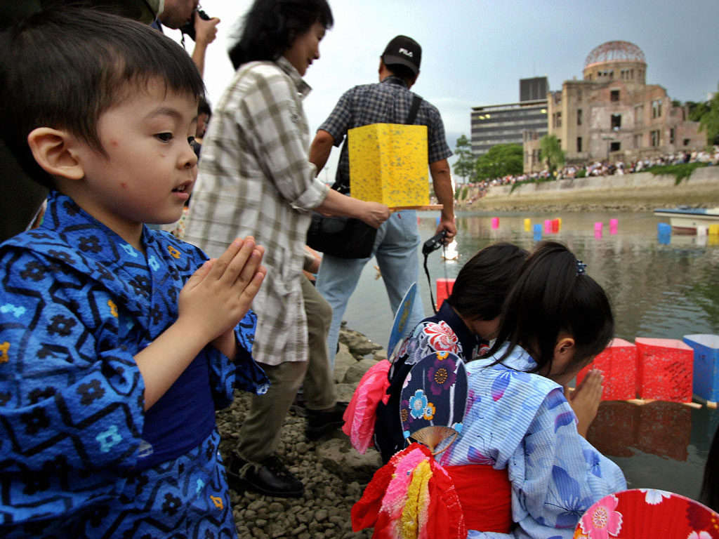 Children release floating lanterns onto the Motoyasu river to pray for relatives victims of the Atom Bomb in front of the Atom Bomb Dome in Hiroshima. Photo by YOSHIKAZU TSUNO / Staff/ Getty images.