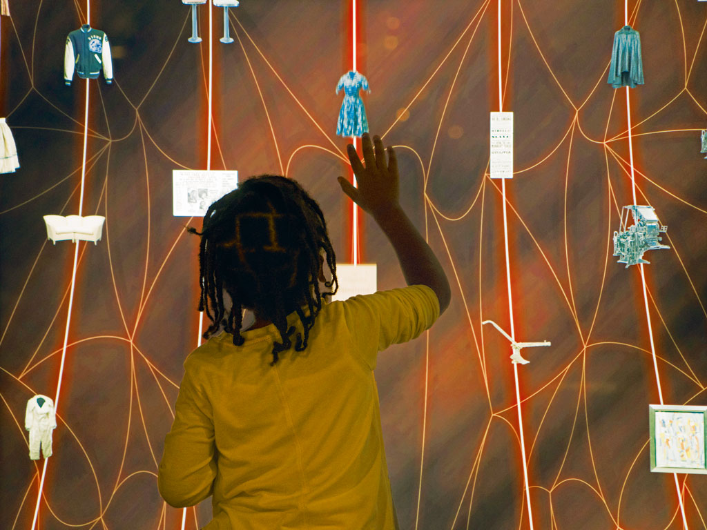) A boy uses an interactive feature at the Smithsonian National Museum of African American History & Culture.