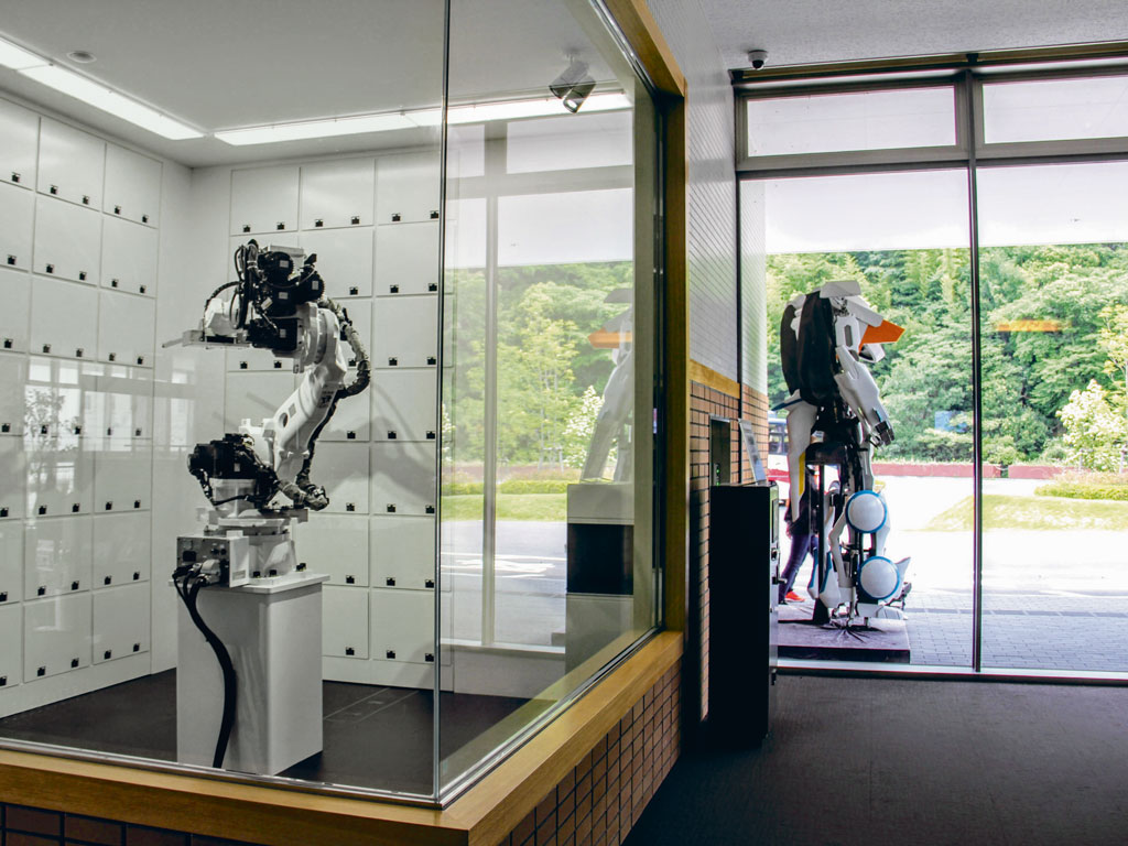 The glass cloakroom has a mechanical arm (bottom right) that retrieves suitcases from a window and places them inside lockers. Photo Courtesy: Henn na Hotel