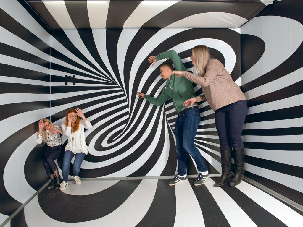 The Ames Room plays with the illusion of size. You see a person shrink or grow in different corners of the room. Photo Courtesy: Museum Of Illusions, Zagreb