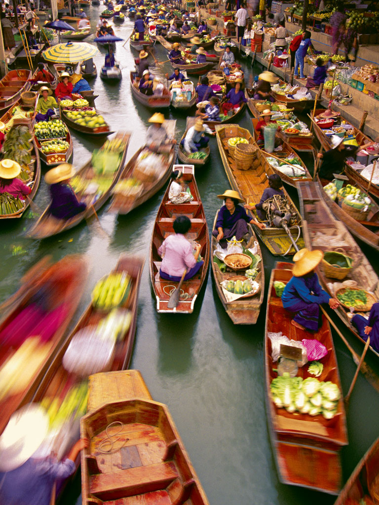 At Damnoen Saduak floating market, in Thailand, it doesn't cost much to sample coconut juice and sweet bananas, then take a canal rowboat tour. Photo by: Design Pics/National Geographic Creative