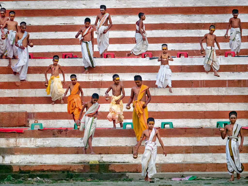 Brahmin students, who are imparted lessons in Vedic lifestyle and culture, run down the red-and-white, candy-striped Kedar Ghat for their morning yoga ritual.
