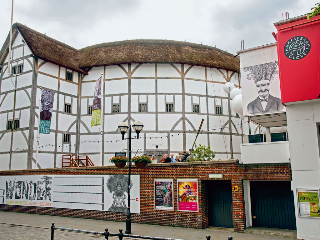 The theatre has a thatched roof and pristinely white facade. Photo by: Education Images/Contributor/Getty Images